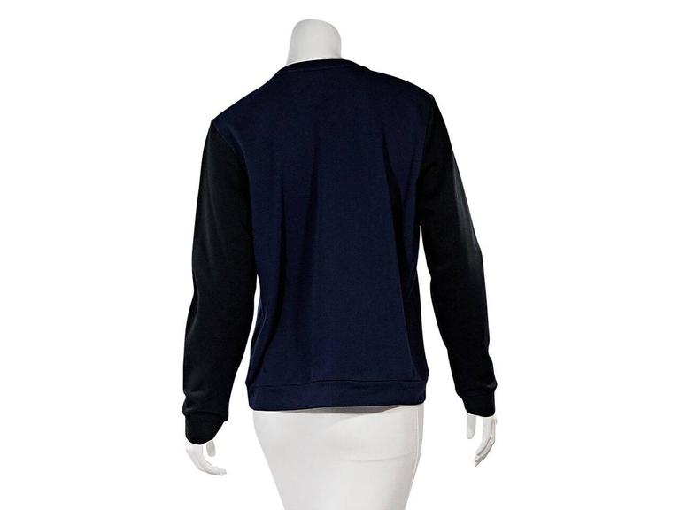 Product details:  Navy blue and black embellished sweatshirt by Lanvin.  Embellished with a tassel rope accents.  Crewneck.  Long sleeves.  Ribbed cuffs.  Pullover style.    Condition: Pre-owned. Very good. Est. Retail $ 748.00