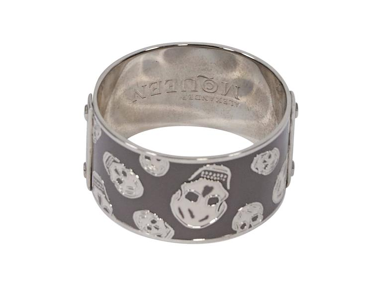 "Product details:  Grey wide bangle bracelet by Alexander McQueen.  Accented with silver-tone skulls.  Slip-on style.  2.7"" diam. x 1.4""H. Condition: Pre-owned. Very good.  Est. Retail $ 395.00"
