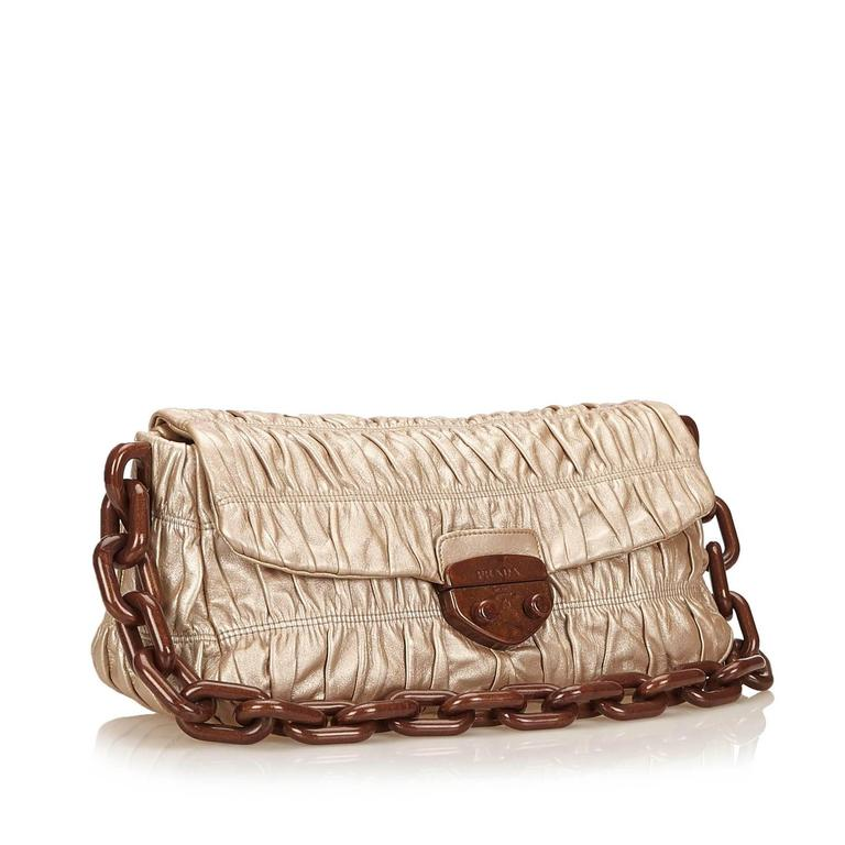 Product details:  Bronze leather nappa gaufre shoulder bag by Prada.  Plastic chain shoulder strap.  Front flap with push-lock closure.  Lined interior with inner zip pocket.  11.8