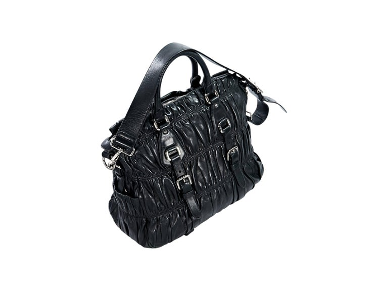 Product details:  Black nappa leather gaufre satchel by Prada.  Dual carry handles.  Detachable, adjustable shoulder strap.  Top zip closure.  Lined interior with inner zip and slide pockets.  Silvertone hardware.  Condition: Pre-owned. Very
