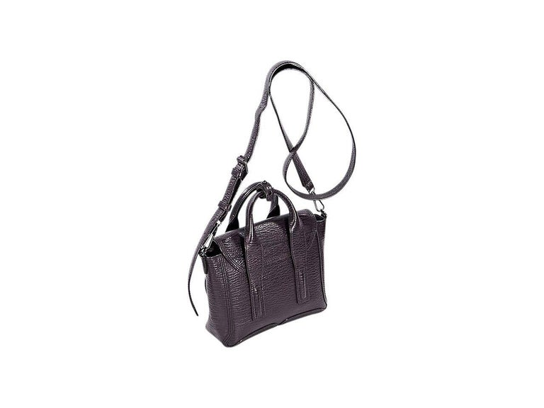 Product details:  Mini eggplant leather Pashli satchel by 3.1 Phillip Lim.  Top carry handles.  Detachable, adjustable crossbody strap.  Front flap with push-lock closure.  Lined interior with inner zip pocket.  Expandable zip sides.  Gunmetal-tone