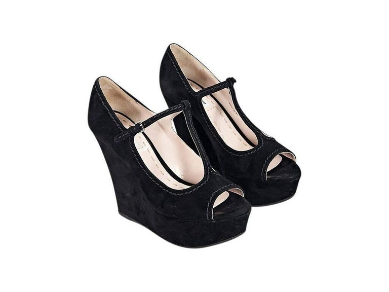 f62bae53efc Product details  Black suede wedge sandals by Miu Miu. Accented with tonal  topstitching.