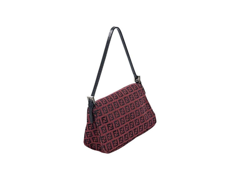 Product details:  Burgundy zucchino baguette shoulder bag by Fendi.  Adjustable single shoulder strap.  Front flap with magnetic snap closure.  Lined interior with inner slide pocket.  Silvertone hardware.  8.25
