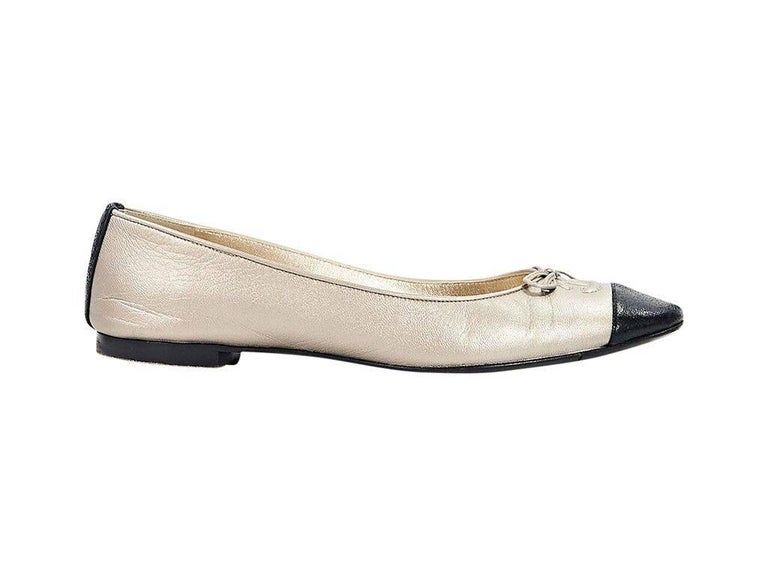 Product details:  Metallic gold leather ballet flats by Chanel.  Bow and embossed logo accent vamp.  Round cap toe.  Slip-on style.  Condition: Pre-owned. Very good. Est. Retail $ 625.00