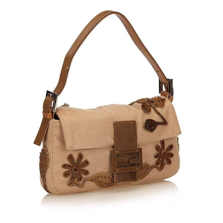 Product details:  Tan wool Baguette shoulder bag by Fendi.  Accented with brown embroidered applique.  Single shoulder strap.  Front flap with buckle strap.  Magnetic snap closure.  Lined interior with inner zip pocket.  Silvertone hardware.  10