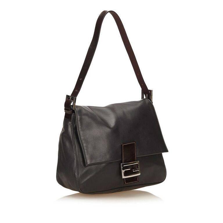 Product details:  Black leather Baguette shoulder bag by Fendi.  Single shoulder strap.  Front flap with logo buckle strap.  Magnetic snap closure.  Lined interior with inner zip pocket.  Silvertone hardware.  Dust bag included.  10.5