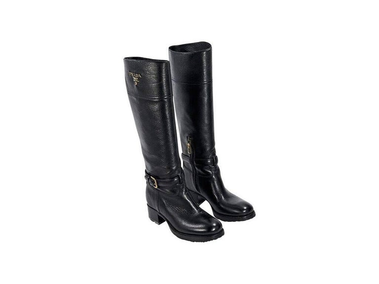 Product details:  Black leather Cervo riding boots by Prada.  Inner half zip closure.  Ankle strap detail.  Round toe.  Chunky stacked heel.  Lug sole.  Goldtone hardware. Condition: Pre-owned. Very good. Est. Retail $ 1,200.00