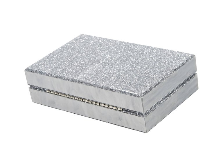 Product details:  Silver glitter box clutch by Ashlyn'd.  Top push-lock closure.  Inner mirror.  Silvertone hardware.  7