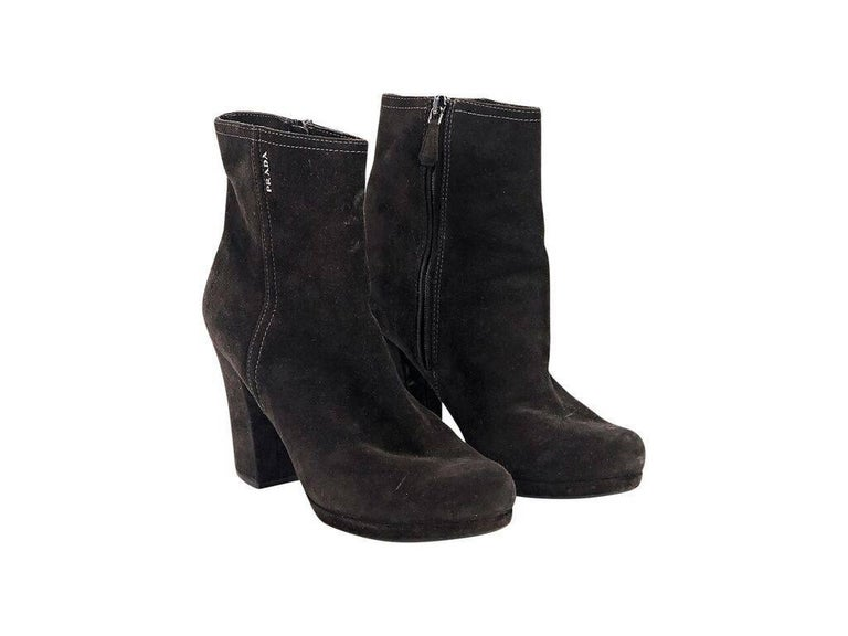 Product details:  Black suede ankle boots by Prada Sport.  Accented with white topstitching.  Inner zip closure.  Block heel and low platform design.  Round toe.  Condition: Pre-owned. Very good. Est. Retail $ 398.00