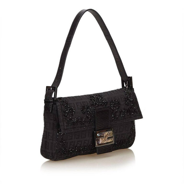 Product details:  Black Zucchino jacquard baguette bag by Fendi.  Embellished with beads.  Single shoulder strap.  Front flap with magnetic snap closure.  Lined interior with inner zip pocket.  Silvertone hardware.  Dust bag included.  10