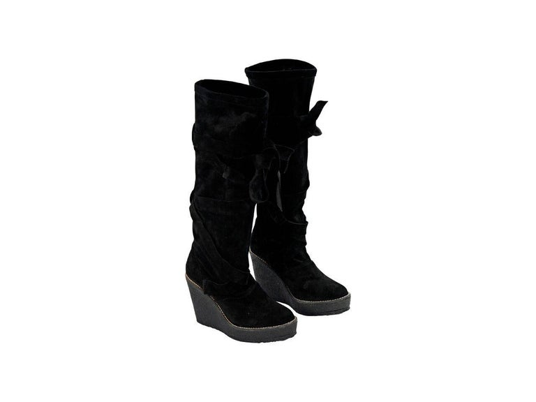 Product details:  Black suede wedge tall boots by Robert Clergerie.  Accented with a wrap-around strap.  Round toe.  Pull-on style.   Condition: Pre-owned. Very good. Est. Retail $ 928.00