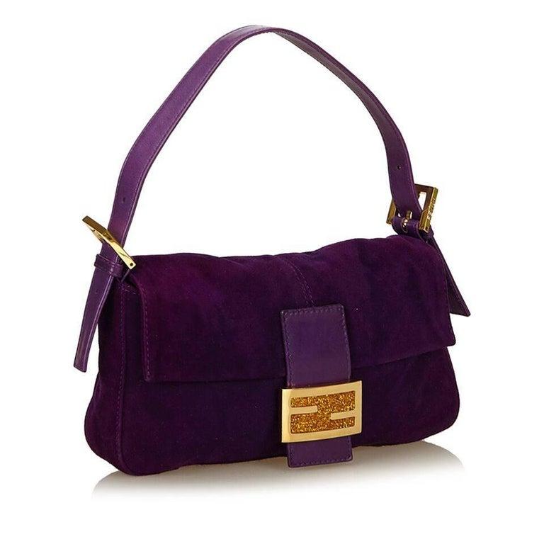 Product details:  Purple nubuck leather baguette shoulder bag by Fendi.  Adjustable single shoulder strap.  Front flap.  Lined interior with inner zip pocket.  Goldtone hardware.  10
