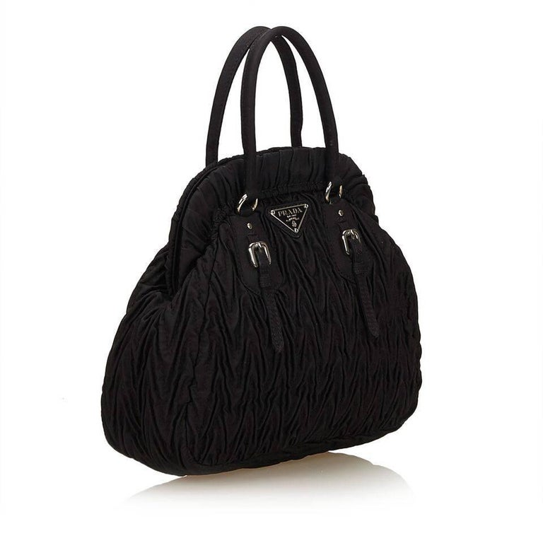 "Product details:  Black gathered nylon handbag by Prada.  Top carry handles.  Hinged top with magnetic snap closure.  Lined interior with inner slide pocket.  Silvertone hardware.  7""L x 7""H x 3""D. Condition: Pre-owned. Very"