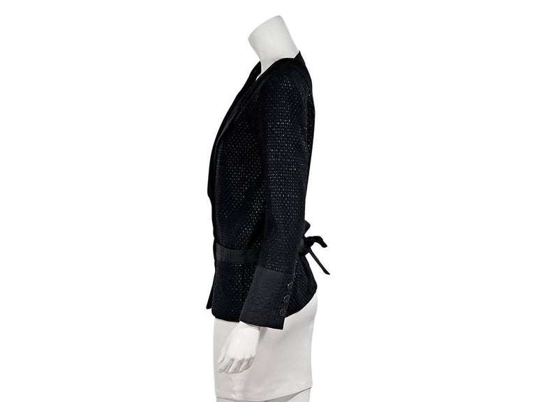 Product details:  Black lattice cotton-blend jacket by Chanel.  Notched lapel.  Long sleeves.  Three-button details at cuffs.  Double-breasted button-front closure.  Waist slide pockets.  Cutout back.  Back waist tie strap.   Condition: Pre-owned.