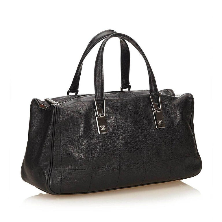 """Product details:  Black caviar leather handbag by Chanel.  Top carry handles.  Top zip closure.  Lined interior with inner zip pocket.  Protective metal feet.  Silvertone hardware.  Dust bag included.  15""""L x 7""""H x 4""""D. Condition: Pre-owned. Very"""