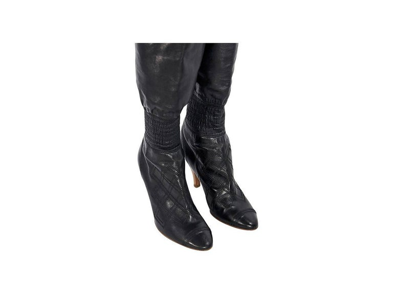 Product details:  Black over-the-knee leather boots by Chanel.  Elastic ankle panel.  Wooden heel.  Round cap toe.  Pull-on style.  Condition: Pre-owned. Very good. Est. Retail $3,275