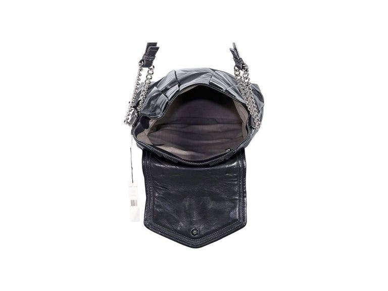 Product details:  Black leather pleated shoulder bag by Marc Jacobs.  Single shoulder strap.  Top flap with magnetic snap closure.  Lined interior with inner zip pocket.  Quilted bottom with white topstitching.  Silvertone hardware.  Authenticity