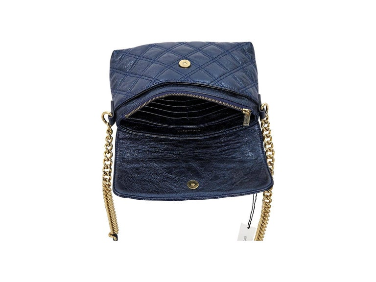 Product details:  Metallic blue quilted leather crossbody bag by Marc Jacobs.  Accented with a faux push-lock closure.  Chain and leather crossbody strap.  Front flap with magnetic zip closure.  Lined interior with multiple inner credit card slots