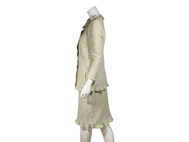 Product details:  Light green tweed skirt suit set by Chanel.  Ruffle-trimmed jewelneck.  Three-quarter length sleeves.  Button-front closure.  Matching skirt.  Banded waist.  Ruffle hem.  Jacket:  36