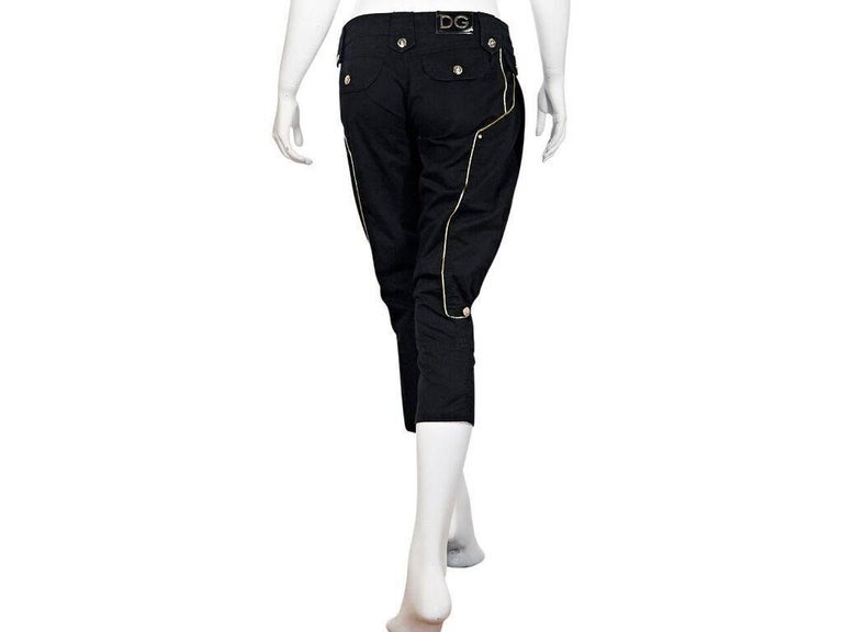 Product details:  Black cropped harem cotton pants by Dolce & Gabbana.  Accented with gold piping.  Banded waist with loops.  Button and zip fly closure.  Front and back button flap pockets.  Goldtone hardware.  28