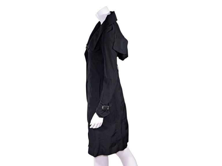 Product details:  Black hooded trench coat by Burberry London.  Spread collar.  Long sleeves.  Adjustable buckle cuff strap.  Concealed snap placket over zip-front closure.  Waist slide pockets.  Back center hem vent.  Label size UK 6.  32