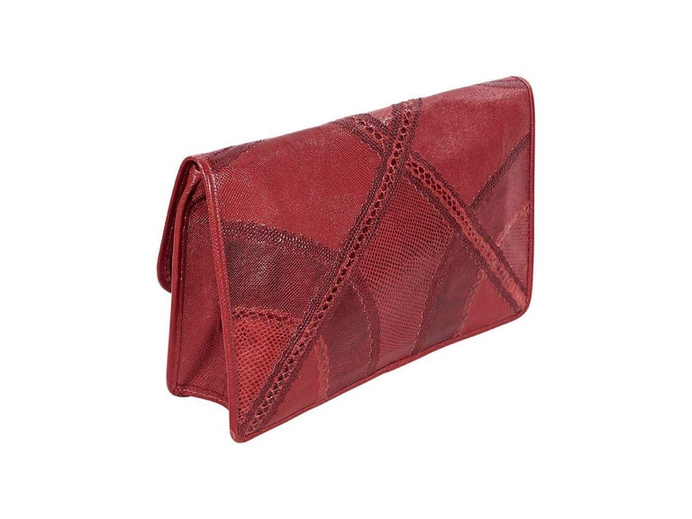 Product details:  Vintage red large exotic skin clutch by Carlos Falchi.  Front flap with concealed magnetic snap closure.  Lined interior with inner slide pocket.  13.25