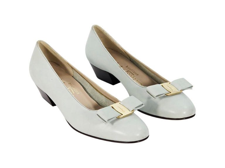 Product details:  Light grey leather ballet flats by Salvatore Ferragamo.  Bow detail at vamp.  Round toe.  Low stacked heel.  Slip-on style.  1.25