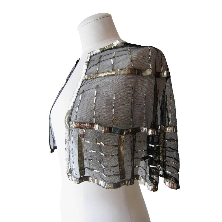 Art deco black tulle cape coverlet beautifully embellished with silver metal rectangle sequins from circa 1920s. Sits on the shoulders and fall down elegantly. Length from neck point to hem : 32 cm