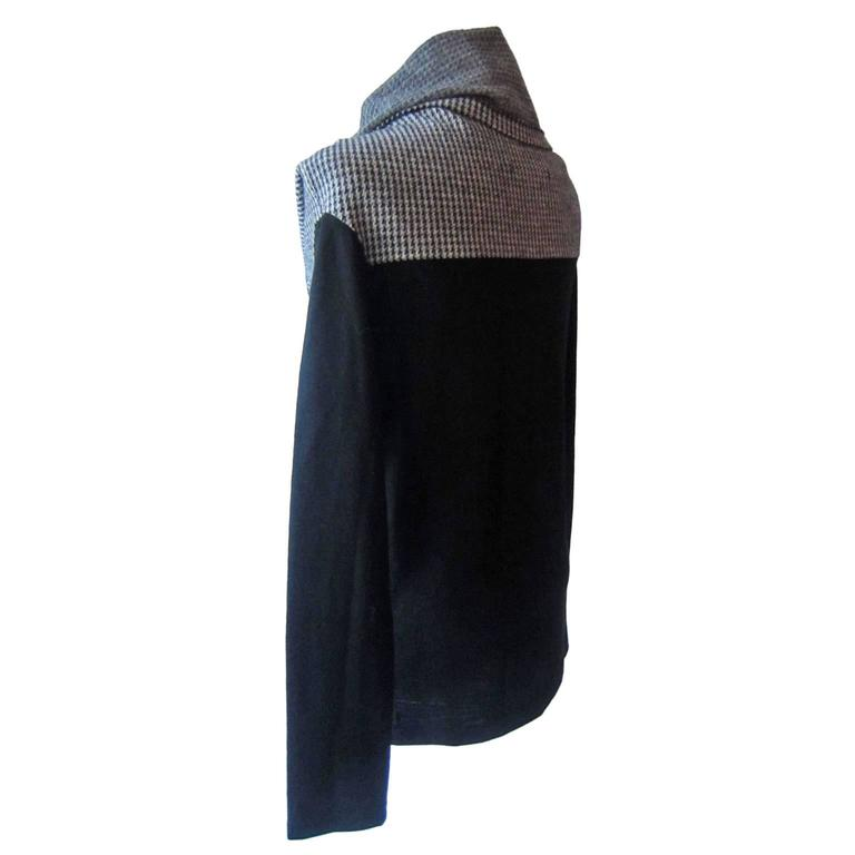 A black turtleneck jumper by Yohji Yamamoto. The jumper is produced in thin wool. It has a loose, fold down turtleneck in light cream and black contrast Pied De Poule pattern fabric. The fabric is soft, and will fall nicely on the