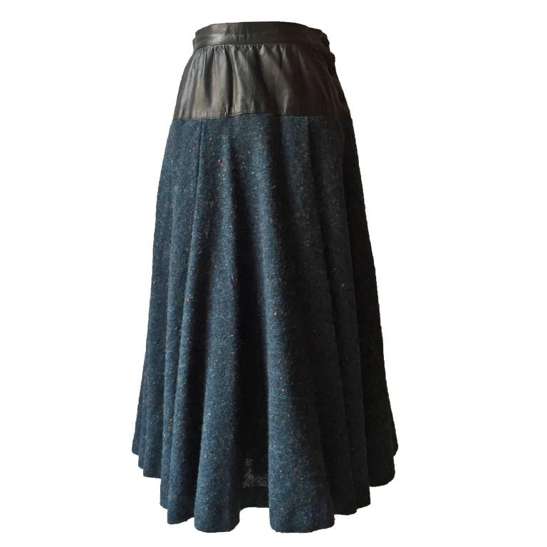 Yves Saint Laurent two toned skirt from 1980s. Dark blue base heavy tweed with leather waist detail, side button closure.  Measurements : Waist : 63 cm Total length 72 cm