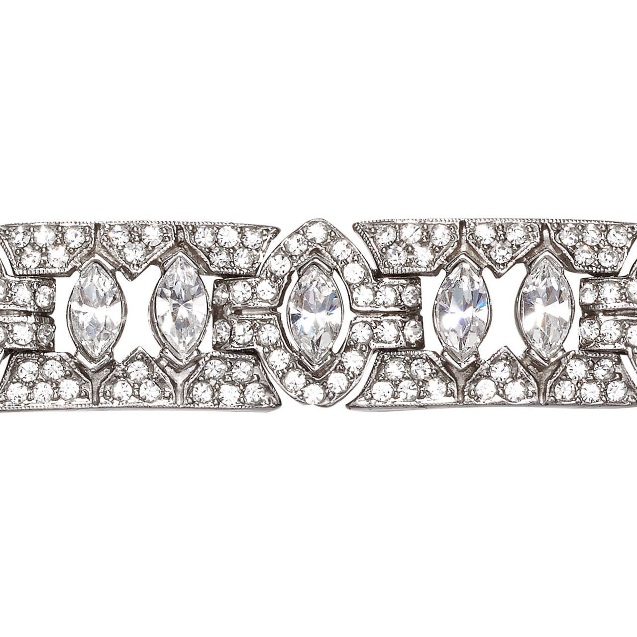 Striking Ciner rhodium plated silvertone bracelet made up of 12x articulated panels, pave set with clear Swarovski crystal rhinestones, in an alternating Art Deco inspired geometric design.  Marked: Ciner (c)