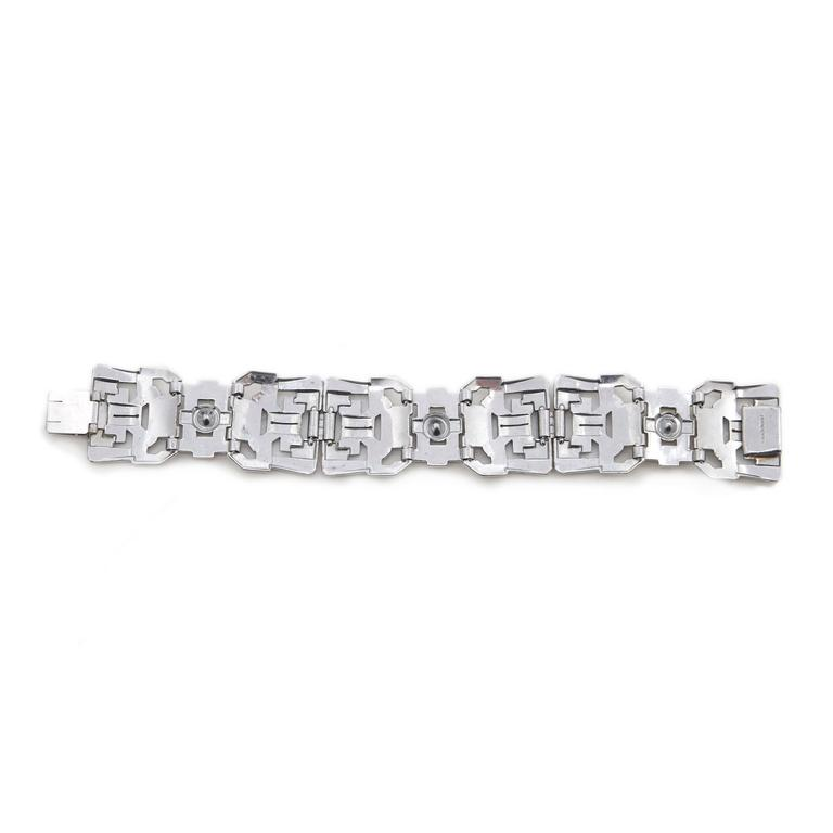 One of the most fantastic Art Deco bracelets we have ever had.  This rare wider width bracelet measures 18cm long, 2.5cm wide.  A genuine Gatsby era bracelet, chrome set with crystal rhinestones and baguettes in a classic pierced openwork