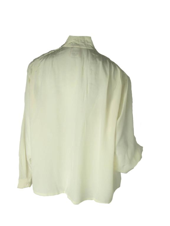 Krizia cream silk blouse with stitching details on shoulders.  Condition: Very good.  Size Large  We accept returns for refund, please see our terms.  We offer free ground shipping within the US.