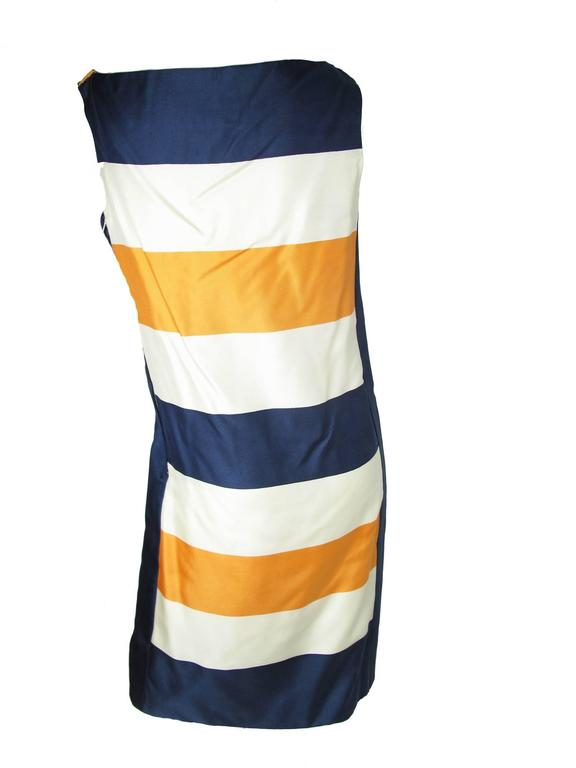 Early 1960s Teal Traina striped silk orange, navy and cream dress.  Two hook and eye on shoulder, zipper down side.  Condition: Very good, small spot on side.  Size Medium We accept returns for refund, please see our terms.  We offer free ground