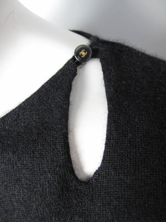 Chanel black cashmere sweater with with one button tear drop opening at neck, bell sleeve with one button closure. Condition: Very good. Size 42 We accept returns for refund, please see our terms.  We offer free ground shipping within the US.