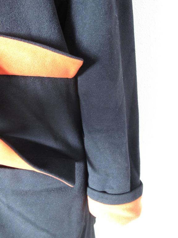 1980s Karl Lagerfeld black wool coat with orange/red under collar, pockets and cuffs. Condition: Excellent. 