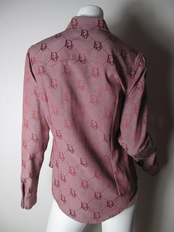 Christian Dior pink cotton, polyester logo cowboy shirt. Snaps to close and on pockets, cuffs. Condition: Excellent. Size 10, F 42  We accept returns for refund, please see our terms.  We offer free ground shipping within the US.  Please let us know