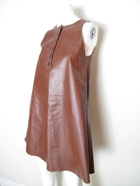 1070s Anne Klein brown leather jumper dress with small pocket and buttons at neckline.  Condition: Very good, some white spots, see photos.  Size 4  We accept returns for refund, please see our terms.  We offer free ground shipping within the US.