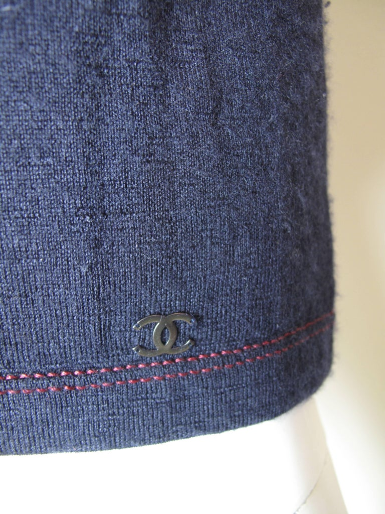 Chanel navy cashmere tee with red stitching.  Condition, good, some wear.  Size 40  We accept returns for refund, please see our terms.  We offer free ground shipping within the US. Please let us know if you have any questions.