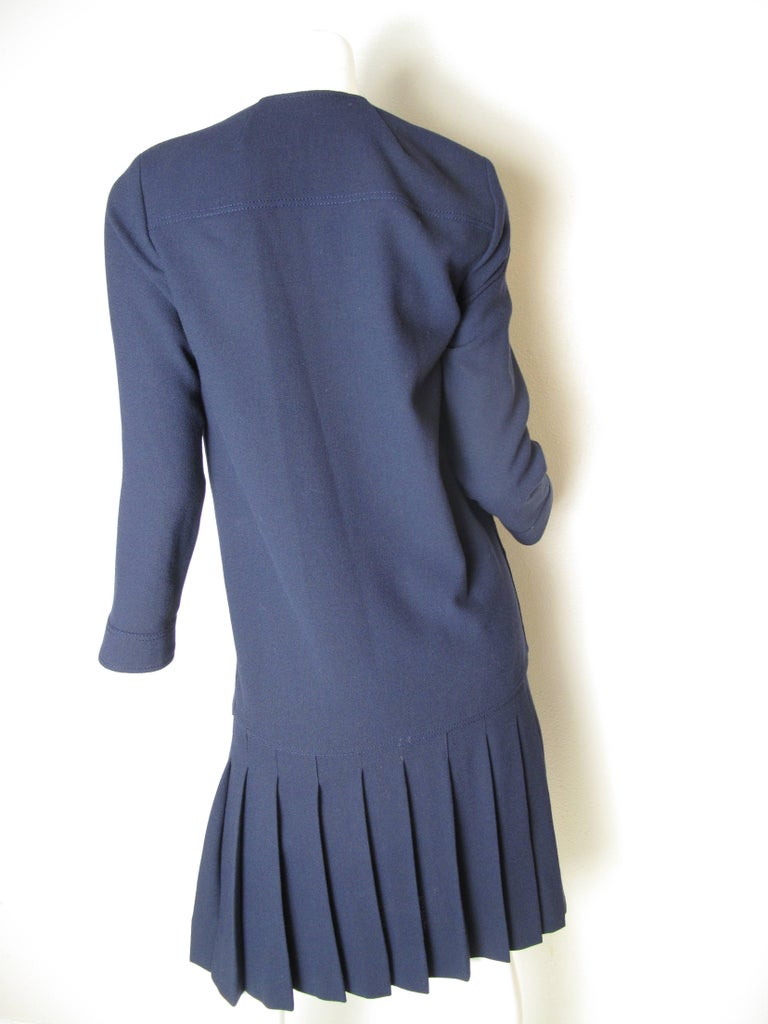 Chanel navy wool suit with pleated skirt. Double breasted jacket.  Condition: Excellent. Size 6   We accept returns for refund, please see our terms. We offer free ground shipping within the US. Please let us know if you have any questions.