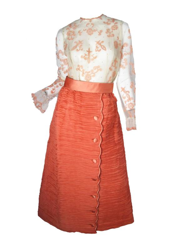 """1960s Sybil Connolly labeled """"softly spoken"""" off white mesh shirt with pink lace overlay.  Pleated Irish linen peachy/pink skirt with buttons down front. Condition: Excellent. Size 10 Top: 36"""" bust, 31"""" waist, 42"""" hips,"""