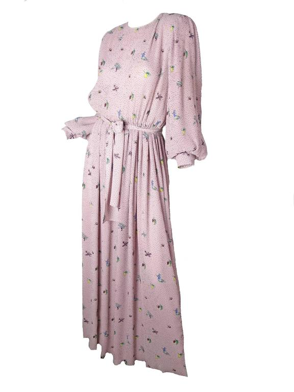 Hanae Mori dusty pink pleated gown with witch, fruit and airplane print.  Belt at waist, tie at neck, button cuffs.  Polyester fabric. Condition: Good, some faint spots on front.  Size 8 /10