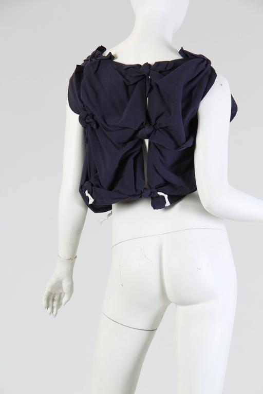 This navy top by famed avant-garde house Comme des Garçons is made of square handkerchief-like pieces knotted together at the corners, resulting in a wonderful texture of round knots and softly draped folds. In between these pieces are open slits