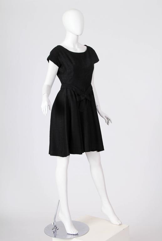 Christian Dior Black Silk Dress. Dress has been altered in the back, it has been made larger with two pieces of fabric set in the waist. This is easily undone and the garment can be back to the original historical style with a pinched in waist. The