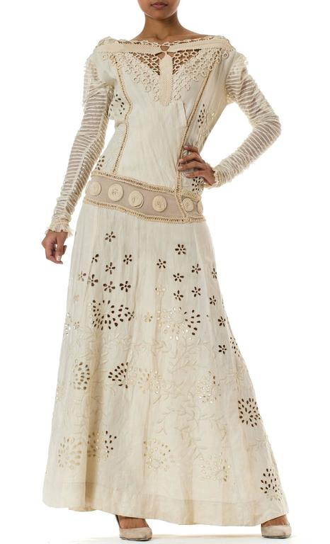 The textiles of this magical dress date from the turn of the century however it's design and construction was altered most likely in the 1970s. Made from a luxurious heavy linen you can't find today it has been entirely embroidered by hand with an