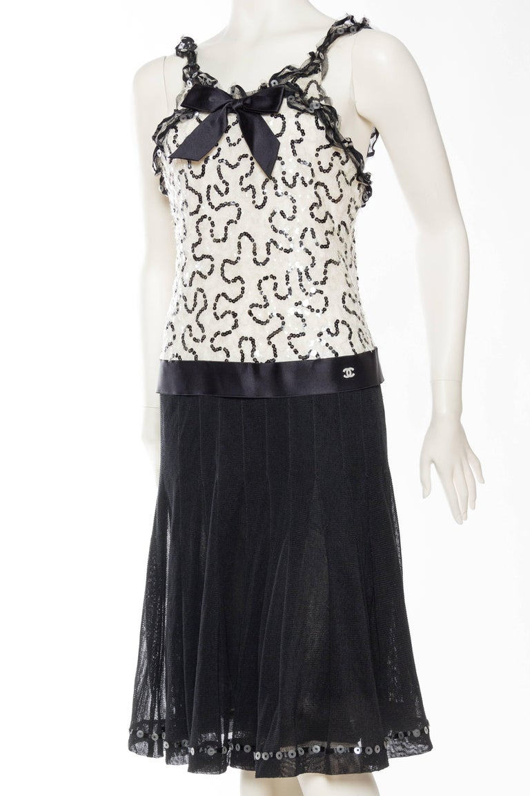 This dress has a fully beaded bodice with clear flower shaped sequins, the symbol of the house, a lovely detail only seen up close. Luscious couture quality silk satin ribbon adorns the neckline and drop waist. Double C logo in carved mother of
