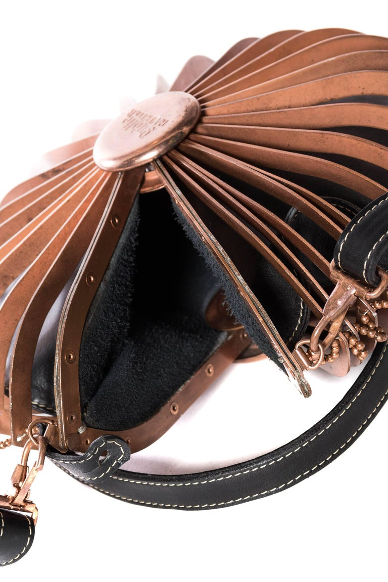 Leather bag inside of a copper cage. Straps are on clips and this can be converted to an over the shoulder bag.