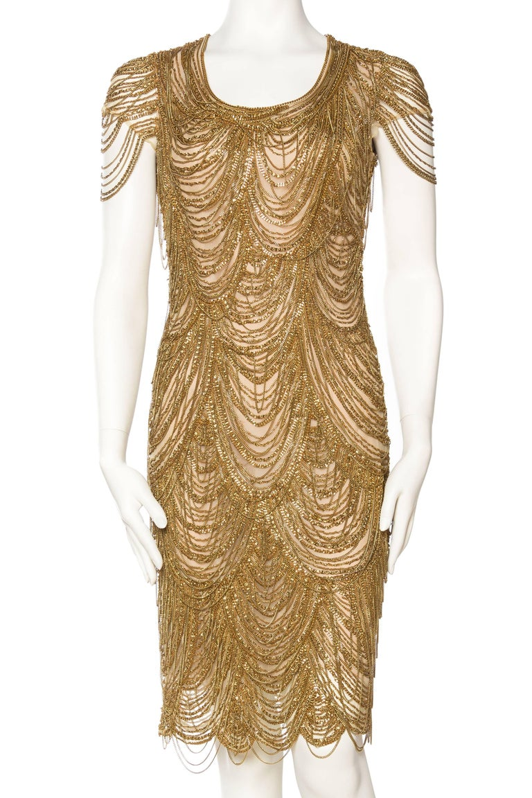 Hundreds of heavy gold chains are both sewn and draped on this dress, which takes it from classic to otherworldly. The sheer nude mesh is lined in silk. The movement of the chains and the golden sparkle of this in person is fantastic.