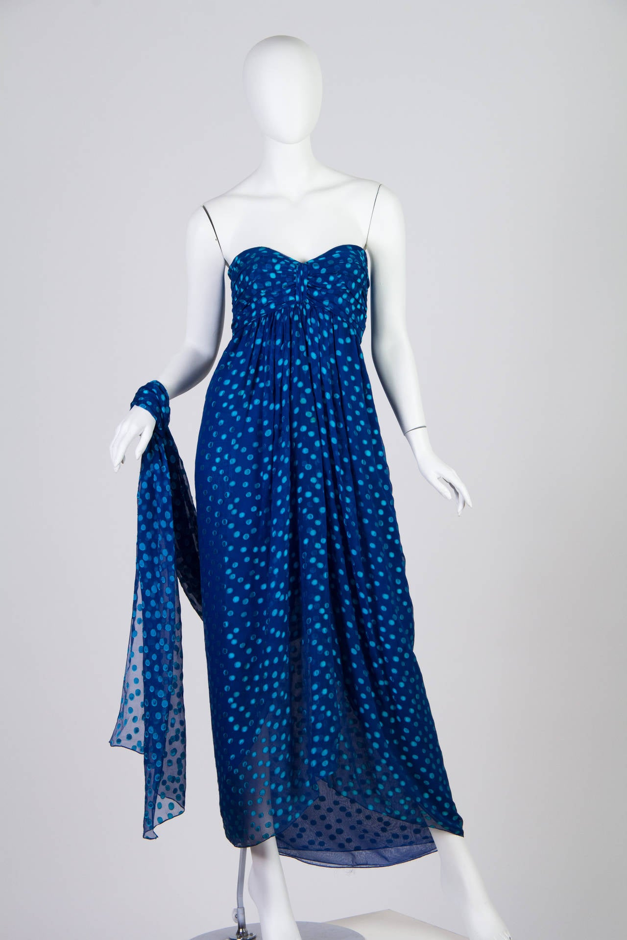 This chiffon gown from Oscar de la Renta for Saks Fifth Avenue is a stunning shade of ultramarine, with shimmering aqua polka dots scattered across it like light dappled on water. Elegant Greek-goddess draping is paired with the fun polka dot