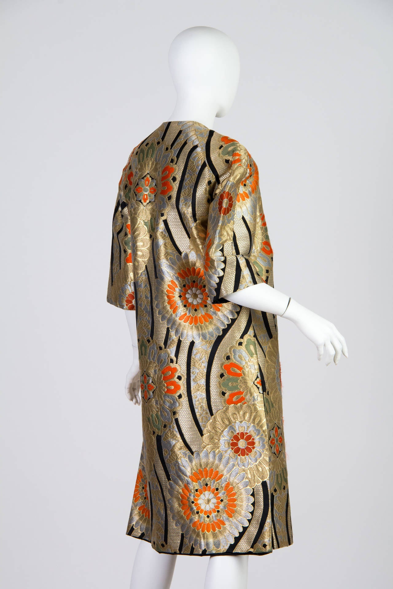 Magical Karabana flowers abound, woven in gold, silver, orange and green. A very special lady in the 1960s saw the magic of this glorious textile and had this beautiful one of a kind opera coat made. The metallic fibers are made with a wash of gold